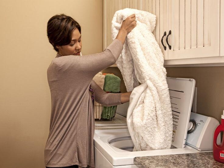 Девушка достает из стиральной машинки плед