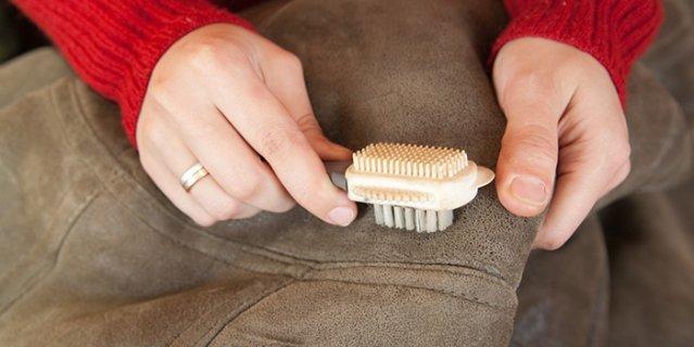 Парень чистит щеткой куртку из замши