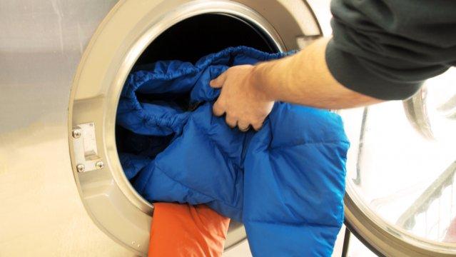 Девушка стирает куртку из холлофайбера в стиральной машине