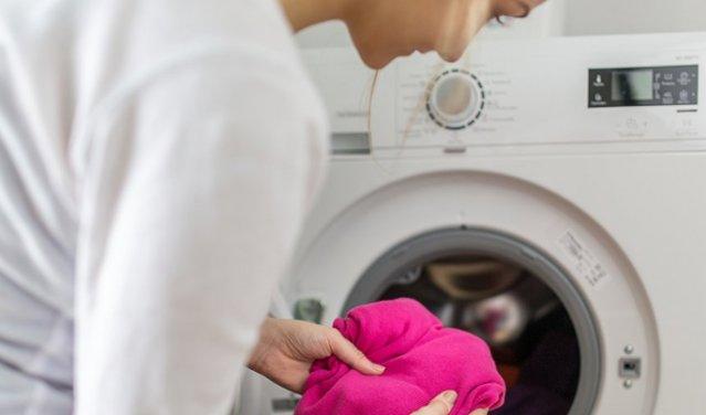 Девушка рядом со стиральной машинкой