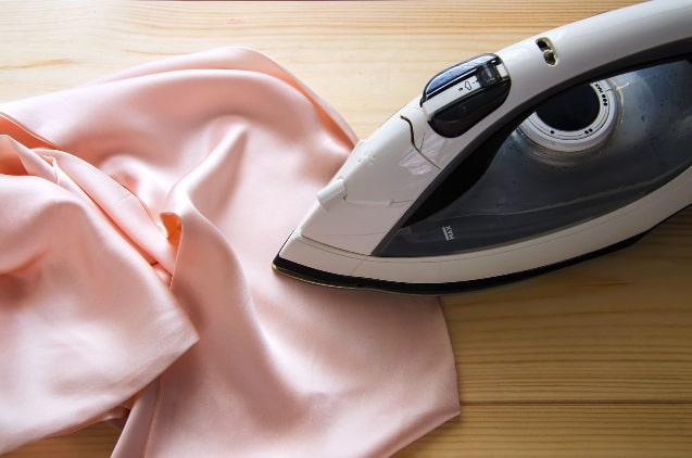 Утюг на гладильной доске с платьем из шелка