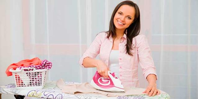 Девушка гладит на гладильной доске