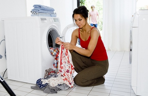 Девушка загружает стиральную машину