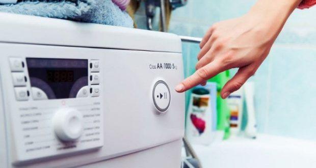 Женщина включает стиральную машинку