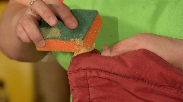 Девушка оттирает пятно с одежды губкой