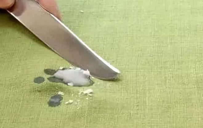 Ножом соскабливают воск с ткани
