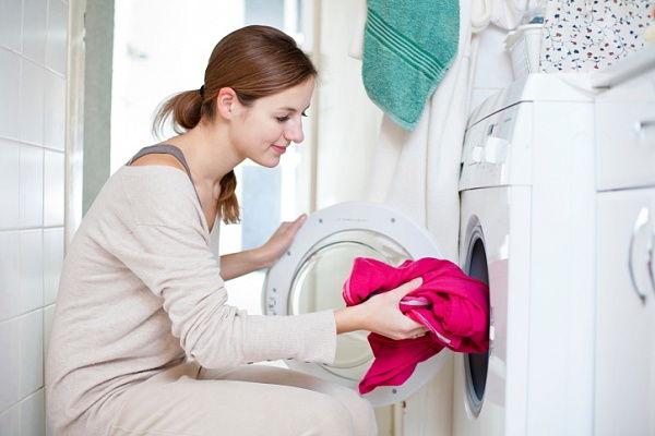 Девушка стирает платье в стиральной машинке