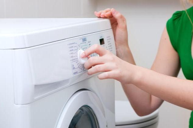 Девушка настраивает режим стиральной машины