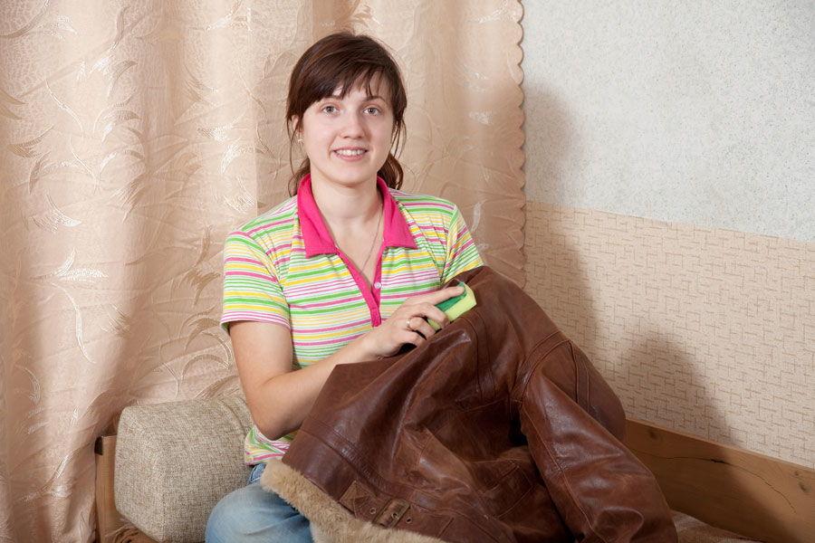 Девушка чистит кожаную куртку